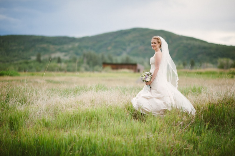 Bride in field and mountain landscape; Steamboat Springs