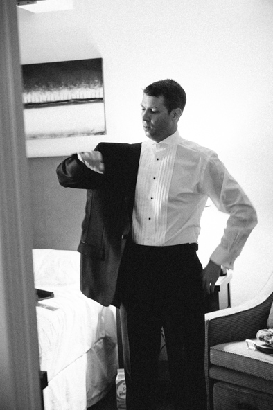 groom putting on tuxedo